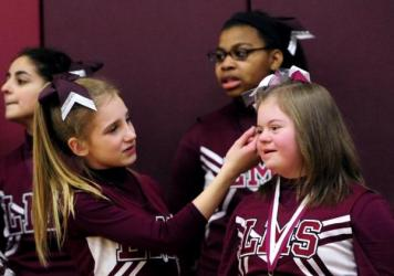 "Alyssa Smith readjusts Desiree Andrews' hair as they cheer for the seventh grade basketball team at Lincoln Middle School on Monday in Kenosha, Wis. The gym has been dubbed ""D's House"" in Desiree's honor."