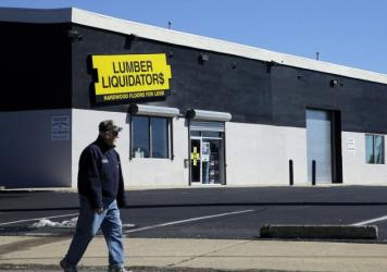 A man walks past a Lumber Liquidators store in Philadelphia. The retailer says it stands by its products and will pay for the safety testing of laminate floors.