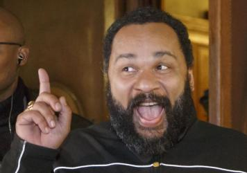 French comedian Dieudonne M'Bala M'Bala gestures to the media as he leaves a Paris court house Feb. 4. He was convicted today of condoning terrorism after the attacks in January in Paris, and given a suspended sentence.