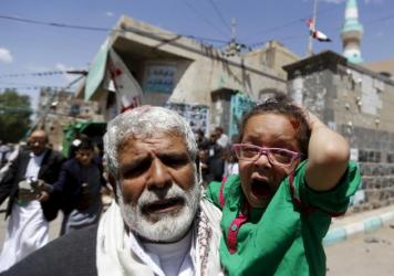 A wounded girl reacts as she is carried by a man out of a mosque that was attacked by a suicide bomber in Sanaa, Yemen, on Friday.