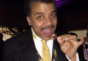 "Neil deGrasse Tyson with a Cambodian cricket rumaki canape, wrapped in bacon. ""I have come to surmise, in the culinary universe, that anytime someone feels compelled to wrap something in bacon, it probably doesn't taste very good,"" he said skeptically before taking a bite."