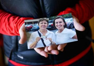 Melinda Townsend-Breslin holds a photo showing her and her mother standing in the parking lot of a favorite thrift store in 2013.