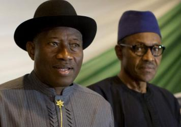 "Nigeria's President Goodluck Jonathan, left, and opposition candidate Gen. Muhammadu Buhari, right, prepare to sign a renewal of their pledge to hold peaceful ""free, fair, and credible"" elections, at a hotel in the capital Abuja, Nigeria, on Thursday."