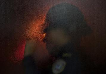 A police office is silhouetted through the emergency room door at a public hospital in San Pedro Sula, Honduras. With 91 murders per 100,000 people, the Central American nation is often called the most violent in the world. The homicide rate is roughly 20 times that of the U.S. rate, according to a 2011 U.N. report.