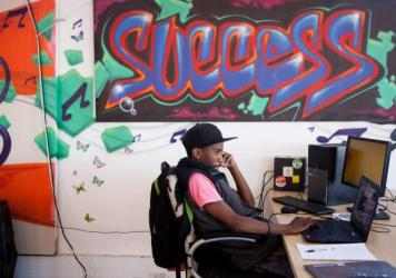 An entrepreneur uses his laptop near graffiti-decorated walls at Hubspace in the Khayelitsha township.