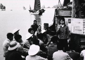 A community worker teaches fishermen about staying healthy.