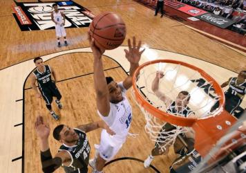 Jahlil Okafor of the Duke Blue Devils goes up for a dunk against Denzel Valentine of the Michigan State Spartans during the NCAA Men's Final Four Semifinal in Indianapolis on Saturday.