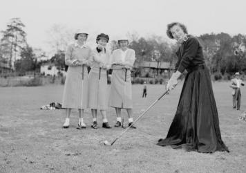 A golfer wears a long black skirt in mock protest of the USGA ban on golfing shorts in tournament play, 1953.