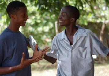 Mohammed Zangar (left) and Amos Tomah find relief from the sun under the leaves of a mango tree.
