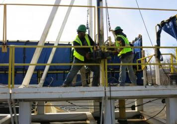 """Students at the Pennsylvania College of Technology are learning a technique called """"tripping pipe,"""" moving a pipe from a stack into a horizontal position and lowering it down into a well.  The students train on a practice drilling rig to learn how to be"""
