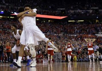 Wisconsin's Frank Kaminsky reacts after drawing an offensive foul on Duke star Jahlil Okafor in the first half of the NCAA college basketball championship game.