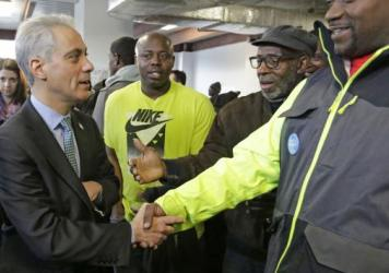 """Chicago Mayor Rahm Emanuel shakes hands at a campaign office Tuesday, as voters gave him a second term. He won a runoff election against Cook County Commissioner Jesus """"Chuy"""" Garcia."""
