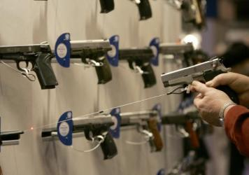 A woman points a handgun with a laser sight at a wall display of other guns during the 2007 National Rifle Association convention in St. Louis.