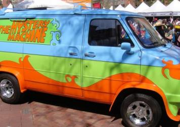 "A replica of ""The Mystery Machine"" van used in the Scooby Doo cartoon series parked at the L.A. Festival of Books in 2012. Hillary Clinton is traveling to Iowa in a van she calls her ""Scooby"" van."