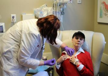 Anne Koller closes her eyes as an oncology nurse attaches a line for chemotherapy to a port in her chest. Koller typically spends three to six hours getting each treatment.