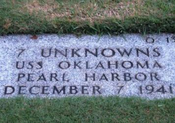 A gravestone identifying the resting place of seven unknowns from the USS Oklahoma is shown at the National Memorial Cemetery of the Pacific in Honolulu. The Pentagon says it will disinter and try to identify the remains of up to 388 unaccounted for sail