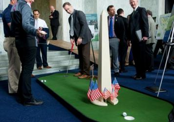 Eric Werwa, left, Deputy Chief of Staff for Rep. Mike Honda, D-Calif., gets some tips on his swing from a PGA professional at the National Golf Day event on Capitol Hill.