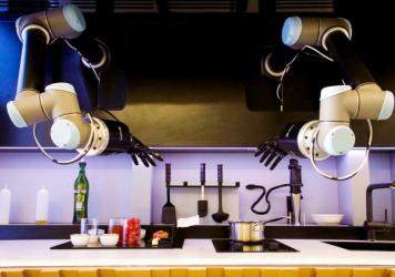 The robotic arms, part of an automated kitchen, hang from the ceiling to prepare dishes. The hands use 20 motors, 24 joints, and 129 sensors to imitate human hands.