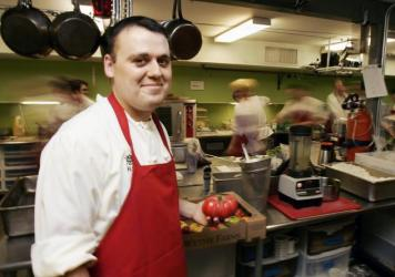 Chef Homaro Cantu holds a tomato in the kitchen of his Chicago restaurant Moto in 2007. Haute cuisine and extreme science collided in the kitchen of Chef Cantu, who took his own life Tuesday.