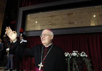 Archbishop Cesare Nosiglia presents the Holy Shroud during a preview for the news media at the Cathedral of Turin, Italy, on Saturday. The shroud — believed by many to be the burial cloth of Christ — will go on display for the first time in five years.