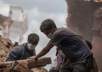 Volunteers clear the debris of a collapsed temple at Basantapur Durbar Square in Kathmandu. The area's reconstruction costs are estimated to be in the billions.