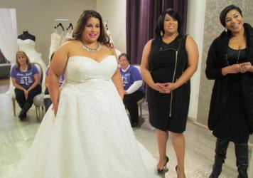 Bride Jennifer Uniglicht tries on a gown at Curvaceous Couture, a bridal boutique specializing in plus-size designer gowns. Proprietors Yukia Walker and Yuneisia Harris (right) star in the new TLC show, <em>Curvy Brides.</em>