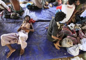 Rohingya refugees sit on a plastic sheet at Matang Raya village, Baktya district in Aceh Utara, Aceh province, Indonesia, on Sunday. Nearly 600 migrants thought to be Rohingya refugees from Myanmar were rescued from two wooden boats stranded off the coas