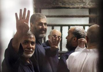 The Egyptian Muslim Brotherhood's third-highest ranking member and a main financier of the banned movement, Khayrat al-Shater (second from left), and other defendants flash the four-finger salute during their trial in Cairo, Egypt, on Saturday. Ousted President Mohammed Morsi, who was among them, received the death penalty.