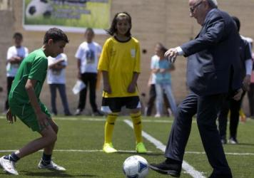 "FIFA President Sepp Blatter kicks a ball during the inauguration of a football stadium in the village of Dura al-Qari near the West Bank city of Ramallah on Wednesday. Blatter said he is on a ""mission of peace"" to resolve tensions between the Israeli and"