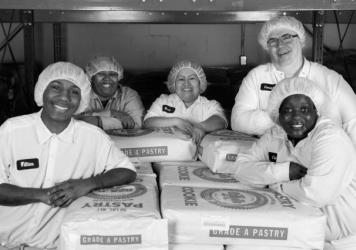 Bakers pose for a photo at the Greyston Bakery in Yonkers, N.Y. For more than 30 years, the industrial facility has been hiring local residents, including people other businesses might consider unhirable.