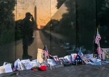 "Army veteran Bernie Klemanek, of Mineral, Va., stops to salute his fallen comrades on Memorial Day during an early morning visit today to ""The Wall"" at the Vietnam War Memorial in Washington."