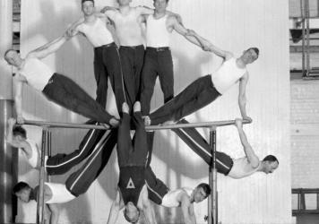 An adult gymnast club performs a group stunt on the parallel bars at the Rochester, N.Y., YMCA at the beginning of the 20th century.