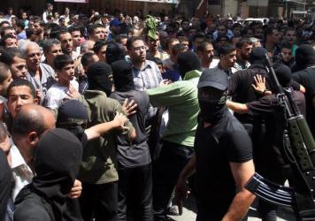 Armed Palestinian masked militants push back a crowd of worshippers outside a mosque in Gaza City on August 22, 2014, before executing more than a dozen men for allegedly helping Israel during its six-week assault on the Palestinian enclave. This week, Amnesty International released a report saying that Hamas was responsible for these and other killings.