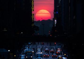 "The sun sets along 42nd Street in Manhattan in 2013 during a semi-annual phenomenon known as ""Manhattanhenge,"" when the sun aligns perfectly with the city's transit grid."