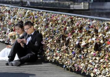 Newlyweds resting on the Pont des Arts in Paris last year. Any hope that the love locks that cling to the famous span over the Seine would last forever will be unromantically dashed by the city council, who plan to dismantle them Monday.