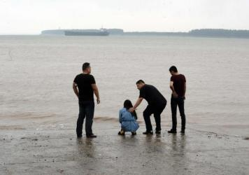 A relative of passengers on board the Eastern Star cruise ship is comforted by a man along the Yangtze River's banks in Jianli, China. Relatives of people missing after the cruise ship capsized have gathered at the disaster site.