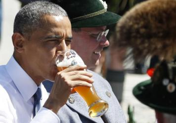 President Obama drinks a beer as he sits between men dressed in traditional Bavarian clothes during a visit to the village of Kruen, southern Germany, on Sunday, prior to the G-7 summit.