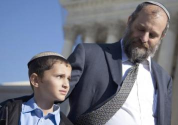 Ari Zivotofsky (right) with his son, Menachem, outside the Supreme Court in 2011. Menachem, now 12, was born in Jerusalem, but the court ruled Israel cannot be noted as the birthplace on his passport.