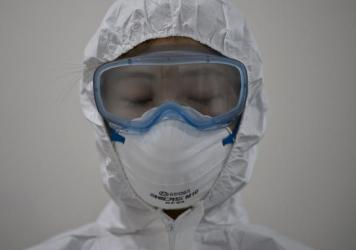 A medical staff member wearing a protective suit waits to enter an isolation ward for patients with Middle East Respiratory Syndrome, MERS, in South Korea.