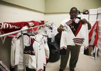 Sam Venable proudly shows off his marching band uniforms at Langston Hughes Academy in New Orleans.