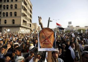 Houthi supporters in Yemen's capital hold up at a defaced poster of the ousted president, Abed Rabbo Mansour Hadi, during a demonstration against air strikes by Saudi Arabia. The Saudis, who have been bombing Yemen since March, are hosting Hadi and other officials from the former government.