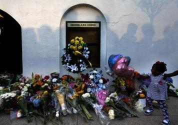 Mourners pass by a makeshift memorial on the sidewalk in front of the Emanuel AME Church in Charleston, S.C.