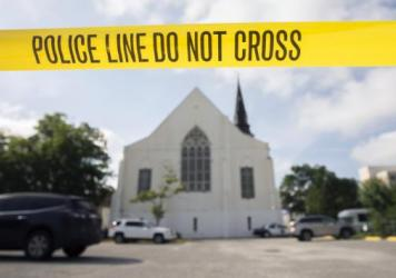 Police tape surrounds the parking lot behind the AME Emanuel Church as FBI forensic experts work the crime scene.