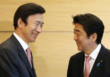 South Korean Foreign Minister Yun Byung-se, left, speaks with Japanese Prime Minister Shinzo Abe at their meeting in Tokyo. The two countries are marking the 50th anniversary of establishing relations. While leaders in both countries stressed the importance of the ties, a bitter history continues to strain the relationship.