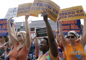 On July 9, 2013, opponents and supporters of a bill to put restrictions on abortion hold signs near a news conference outside the Texas Capitol in Austin. The bill was passed, but has been battled in the courts for two years; now, the law is set to go in