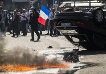 An UberPop vehicle was overturned by French taxi drivers who also clashed with riot police, during Thursday's protest of the app-based ride-hailing company.