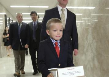 Leukemia survivor Rhett Krawitt, 7, carries a box of petitions representing more than 30,000 people supporting a measure requiring nearly all California schoolchildren to be vaccinated. He took them to the governor's office at the Capitol in Sacramento,
