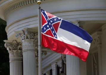 The state flag of Mississippi is unfurled against the front of the Governor's Mansion in Jackson, Miss., on Tuesday. The flag has been the center of renewed controversy since last week's racially motivated shooting of nine parishioners at a black church