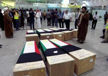 People gather near flag-draped coffins of Kuwaiti Shiite victims from Friday's suicide bombing at a mosque in the capital.