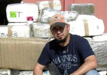 Jonathan Treviño poses in front of a drug bust.